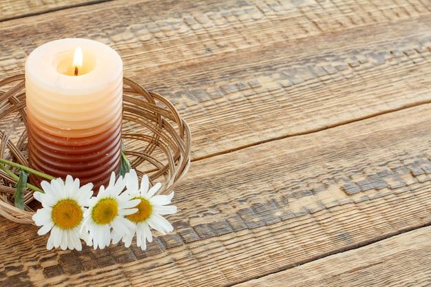 나무 판자에 있는 고리버들 바구니에 촛불과 카모마일 꽃다발을 태우세요. 평면도. 휴일 개념입니다.