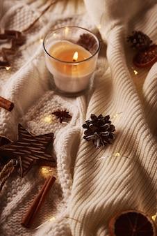 Горящая свеча и рождественские украшения. зимний уютный дом и концепция хюгге