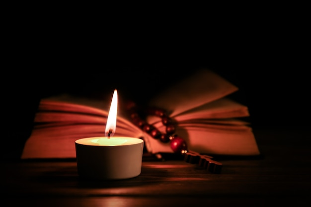 Burning candle and bible on wooden table
