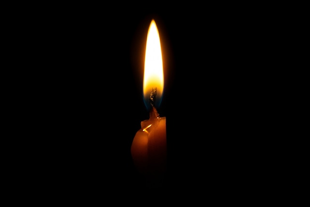 Burning candle on black background