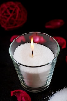 Burning candle on a black table