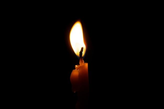 Burning candle on black