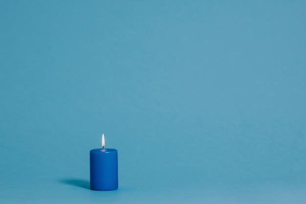 Burning candle in blue color