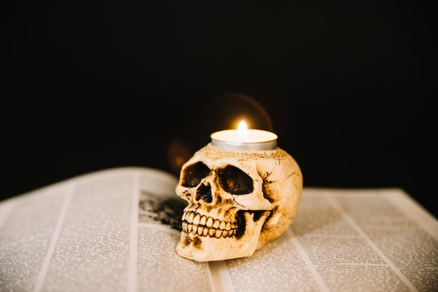 Burning candle and book of black magic