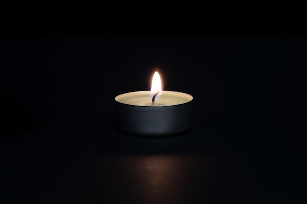 A burning candle on a dark background with a flare in the foreground. layout, mockup.
