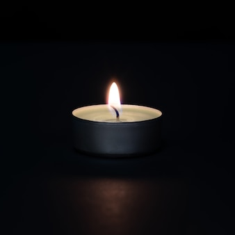 A burning candle on a dark wall with a flare in the foreground.