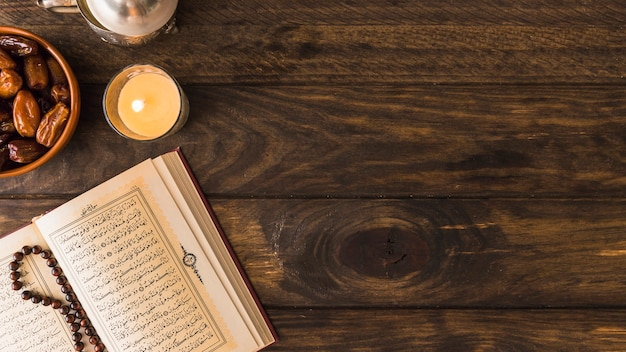 Burning candle and dates near religious book