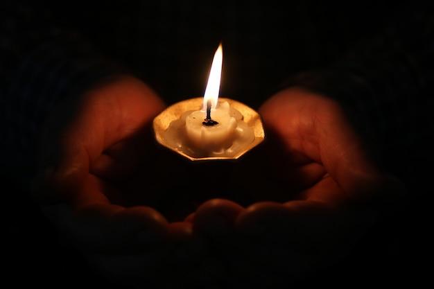 남자 손 종교 개념에 촛불을 굽기