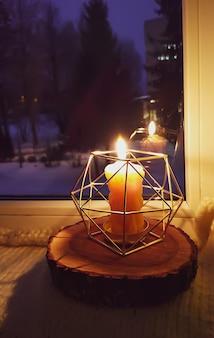 실내 창틀에 있는 현대적인 금속 촛대에 촛불을 태웁니다.