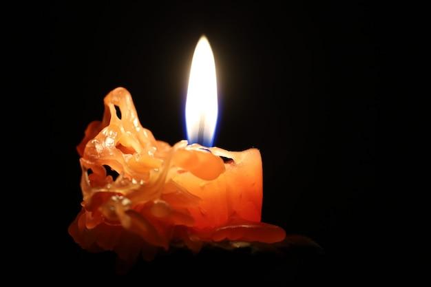 Горящая свеча в темноте крупным планом