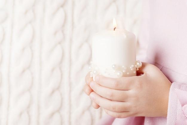 Горящая свеча в руках девушки. рождественская свеча. рождественский декор. руки ребенка держат красивую свечу с огнем. копировать пространство