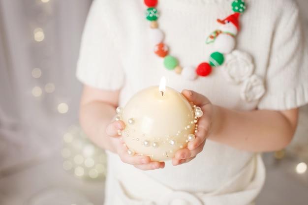Горящая свеча в руках девушки. рождественская свеча. рождественский декор. руки ребенка, держа красивую свечу с огнем. копировать пространство