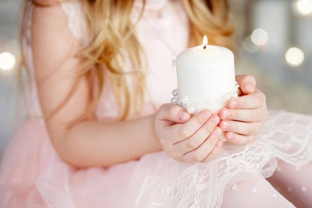 Горящая свеча в руках девушки.
