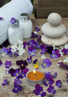 紫のパンジーの花の真ん中で燃えるろうそくとスキンローションがセットされたスパ