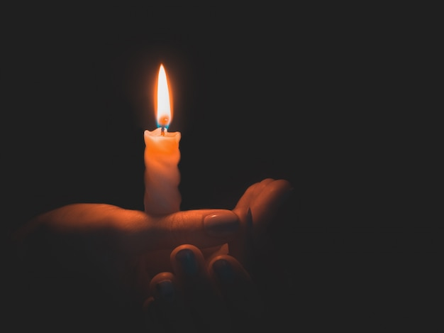 Burning candle in male hand