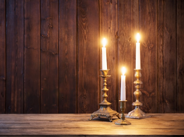 Burning candle on old wooden wall