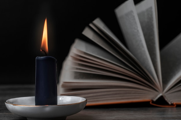 Burning candle and an open book. set for witches.