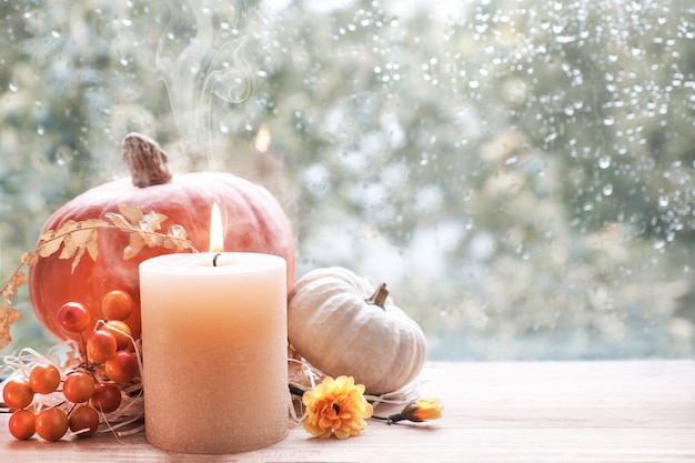 Burning candle, pumpkin and fall decorations on a window