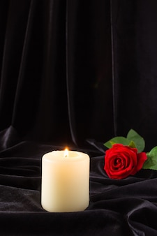 A burning candle and a red rose on a black background