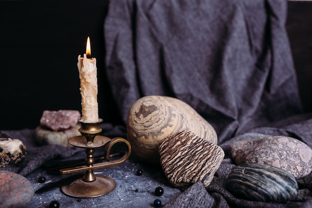 Burning candle and stones on the witch table occult esoteric concept