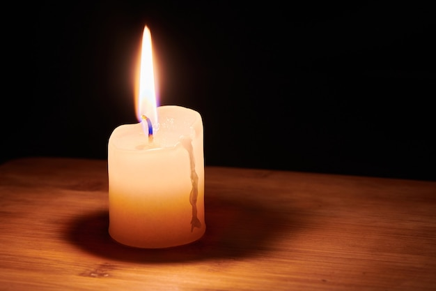 Burning candle on the table in night dark. flame of the hope and memory.