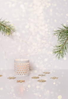 Burning candle in a white ceramic candlestick. minimalistic christmas background. selective focus, blurred image.