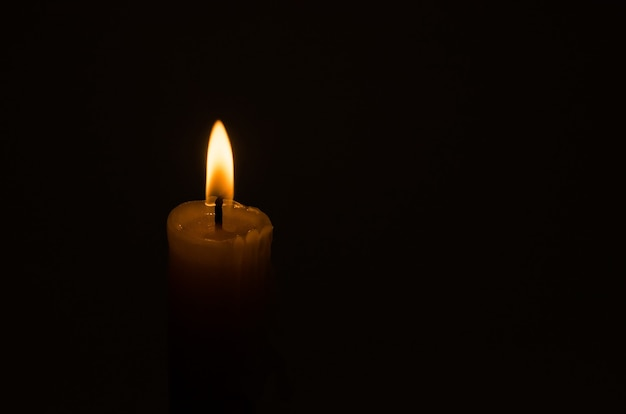 Горящий фитиль свечи на черном фоне с копией пространства, печали и траура.