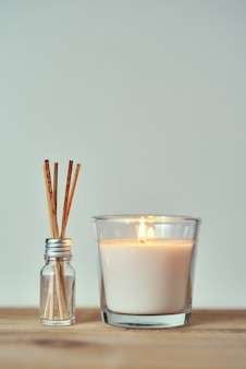 Burning candle with aroma sticks in glass bottle