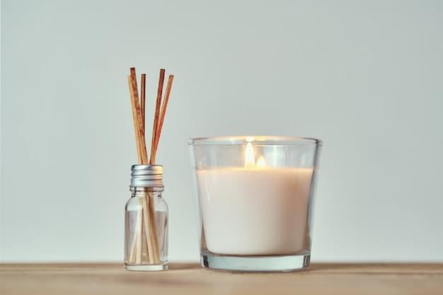ガラス瓶にアロマスティックで燃えているキャンドル