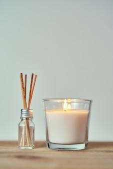 ガラス瓶の中のアロマスティックで燃えているキャンドル