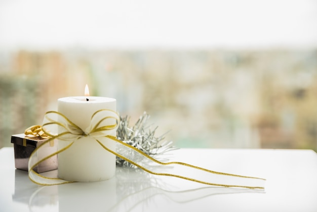 Burning candle with bow near window