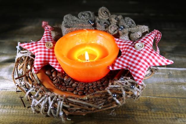 色の木製の背景にクリスマスの装飾と燃えるろうそく