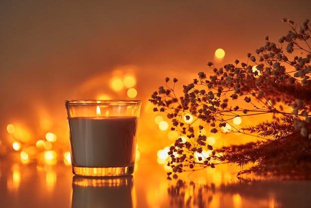 Burning candle with dried plant against blurred golden lights on dark