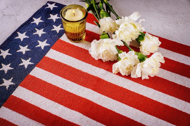 Burning candle with flowers on us flag surface