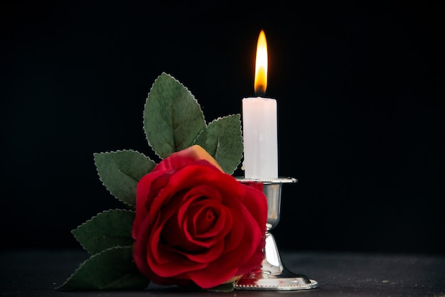 Burning candle with red flower as memory on a dark surface
