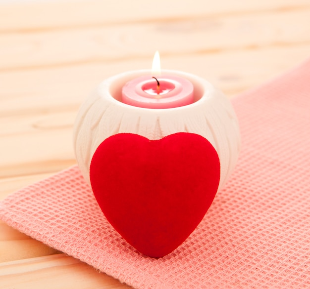 Burning candle with red heart