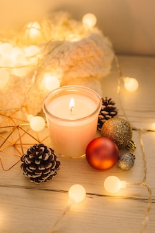 Burning candle with scarf on wooden table