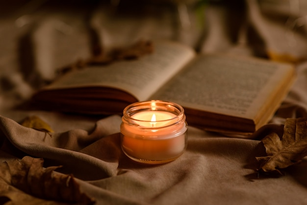 A burning candle on a wooden table in front of a book in a half-mast. learning. studying the bible