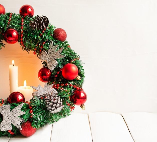 불타는 초 및 빨간 공 및 복사 공간 소나무 콘 크리스마스 화 환