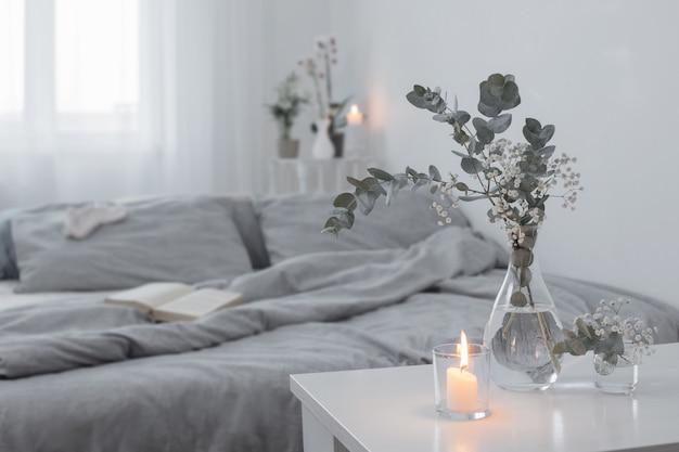 화이트 침실에 유리 꽃병에 촛불과 유칼립투스 굽기