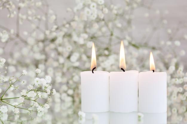 Горящие свечи и белые цветы гипсофилы на столе с пространством для текста. красивые идеи декора.