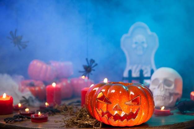 Горящие свечи на праздновании хэллоуина с жуткой тыквой рядом. таинственный туман.