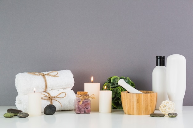 Burning candles and beauty products in front of grey wall