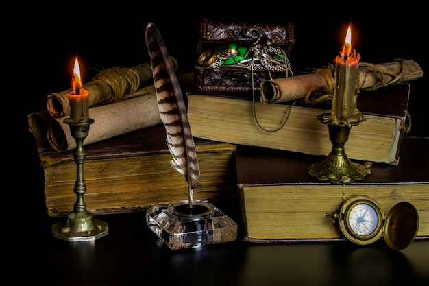 Burning candles in bronze candlesticks, a glass inkwell with a feather, large old books and a chest with jewelry on a black background.
