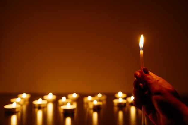 Burning candles. candle in female hands. many candles burning at night. many candle flames glowing.