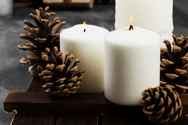 Burning candles and christmas attributes on a dark surface