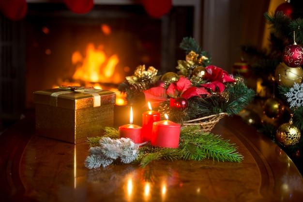 リビングルームの燃える暖炉の隣のテーブルに燃えるキャンドル、クリスマスリース、金色のギフトボックス。焦点深度が浅い画像。
