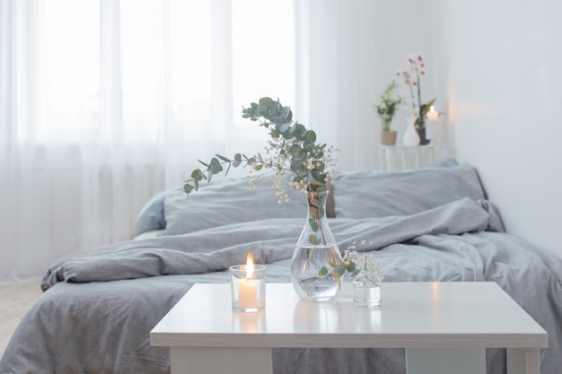 Burning candles and eucalyptus in glass vase in white bedroom