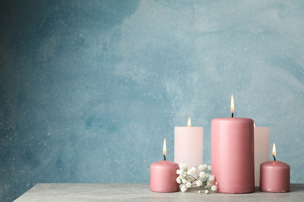 Burning candles and flower against blue, space for text