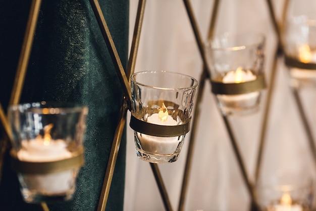 Горящие свечи в стеклянных подсвечниках крепятся металлической решеткой к стене. украшение банкетного зала.